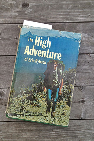 The cover of the High Adventure on Eric Ryback, hiking with mountains in the background