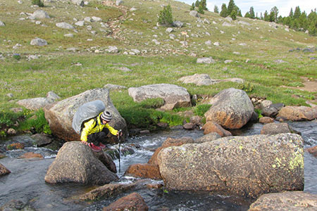 Hiker crossing Washakie Creek on boulders