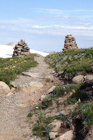 rocky trail running between two rock cairns toward a snowfield